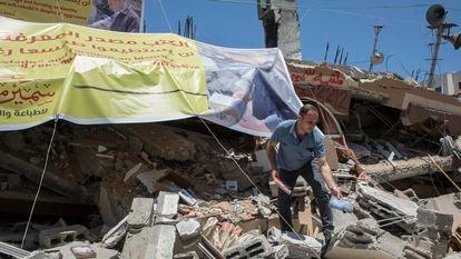 Um palestino resgata livros entre os escombros da livraria Mansur, destruída por um bombardeio israelense, em maio em Gaza.