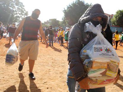 Personas cargan bolsas de plástico con ayuda alimentaria distribuida por el