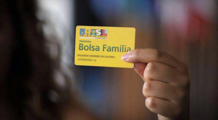 Beneficiária do programa de transferência de renda do Governo segura um cartão do Bolsa Família.