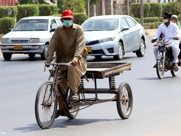 Karachi (Pakistan), 17/06/2020.- Residents wearing protective face masks on a road in Karachi, Pakistan, 17 June 2020. Countries around the world are taking increased measures to stem the widespread of the SARS-CoV-2 coronavirus which causes the Covid-19 disease. EFE/EPA/REHAN KHAN