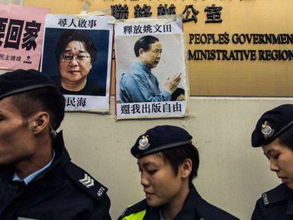 Policiais ao lado de cartazes de dois desaparecidos.