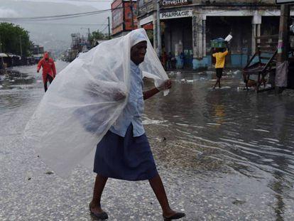 Mulher se protege da chuva na terça-feira em Porto Príncipe, no Haiti.