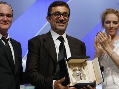 O diretor turco Nuri Bilge Ceylan recebe a Palma de Ouro ao lado do diretor Quentin Tarantino e da atriz Uma Thurman.