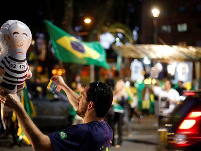 Um homem segura o 'Pixuleco', o balão do ex-presidente Lula vestido como um réu em uma manifestação em Curitiba.