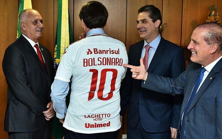 Presidente do Inter (à esq.) presenteia Bolsonaro com uma camisa colorada, em março de 2019.