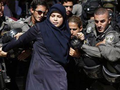 As forças de segurança israelenses detêm uma mulher palestina.