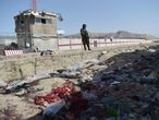 A Taliban fighter stands guard at the site of two powerful explosions, which killed scores of people including 13 US troops on August 26, at Kabul airport on August 27, 2021. (Photo by WAKIL KOHSAR / AFP)