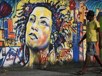Homem caminha em frente a um mural de Marielle Franco, no Rio de Janeiro.