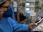 -FOTODELDIA- AME5595. SÃO LEOPOLDO (BRASIL), 25/03/2021.- Una enfermera sostiene un teléfono durante una videollamada entre un paciente con covid-19 y sus familiares, en la Unidad de Cuidados Intensivos del Hospital Centenario el 22 de marzo de 2021 en Sao Leopoldo (Brasil). Un grupo de enfermeros en Sao Lepoldo, sur de Brasil, busca reducir la angustia de familiares de pacientes con covid-19 a través de videollamadas, reportando el estado de salud y animando desde la distancia. EFE/Daniel Marenco
