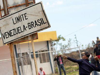 Jovem atira pedra contra policiais da Guarda Nacional venezuelana, em setembro de 2019, na fronteira de Brasil e Venezuela.