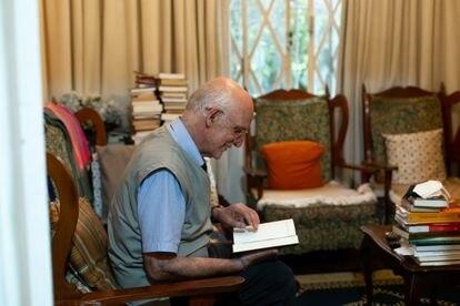 O padre Julio Lancellotti manuseia um livro na sala de sua casa, em São Paulo.