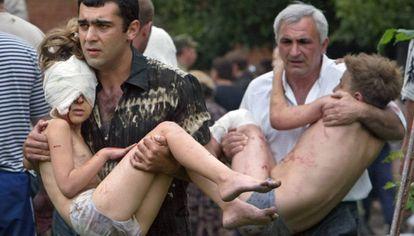 Dois homens carregam crianças resgatadas após a ação das forças russas em Beslan, em 2004 (arquivo).