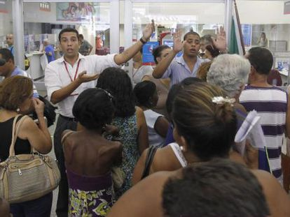 Funcionários pedem calma a clientes em uma agência do Bradesco no Rio de Janeiro.