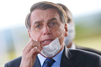 O presidente Jair Bolsonaro remove sua máscara para conversar com apoiadores
