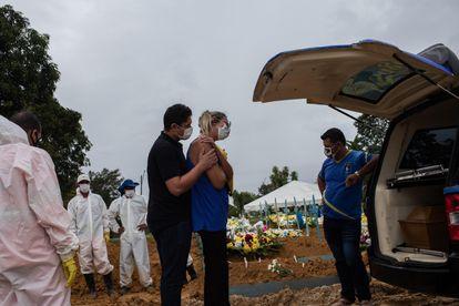 Dois familiares participam do enterro de uma vítima da covid-19 no Cemitério de Nossa Senhora Aparecida em Manaus.