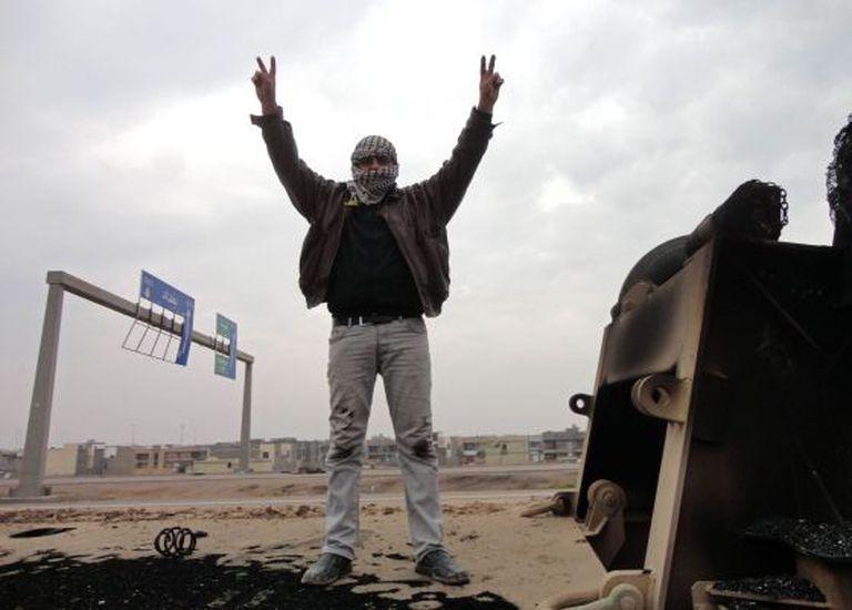 Um rebelde faz o sinal da vitória em uma estrada de Fallujah, no Iraque.