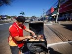 A man barbecues in his street food stall on a street in the Ceilandia neighborhood, amid the coronavirus disease (COVID-19) outbreak, in Brasilia, Brazil July 7, 2020. Picture taken July 7, 2020. REUTERS/Adriano Machado
