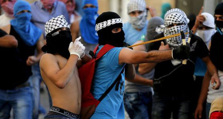 Palestino joga pedras contra a polícia israelense.