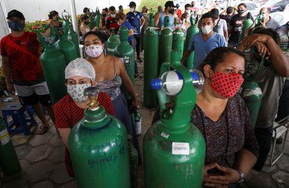 Familiares de enfermos con graves problemas respiratorios hacen cola ante una empresa que rellena los cilindros con oxígeno en Manaos el pasado martes.
