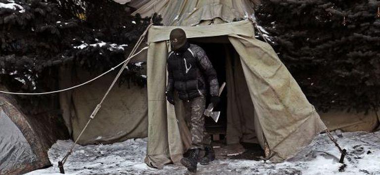 Um manifestante ucraniano sai de uma barraca na Praça da Independência, em Kiev.