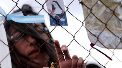 Mulher reza em frente à base naval de Mar del Plata, onde são esperados os 44 marinheiros perdidos no Atlântico