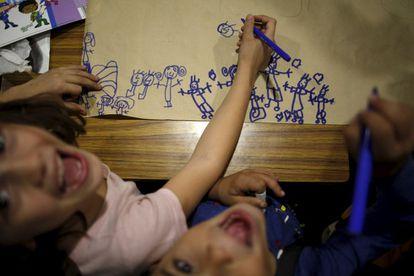 Crianças sorriem enquanto fazem desenhos infantis em Puente Tocinos em Murcia (Espanha), em 3 de novembro de 2015.