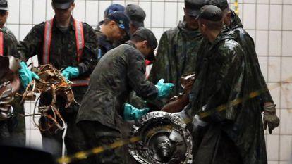 Membro das Forças Armadas recolhem pedaços do avião.