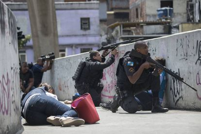 Moradores tentam se proteger de tiroteio em passarela da Rocinha enquanto policiais trocam tiros com traficantes no Rio.