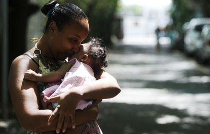 Brasileira carrega a filha afetada pelo vírus Zika.