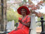 Una mujer mayor ataviada con sombrero disfruta en solitario de un día de sol en el Queen's Park Savannah, el principal parque de Puerto España (Trinidad y Tobago), pese a las restricciones y la orden de quedarse en casa.