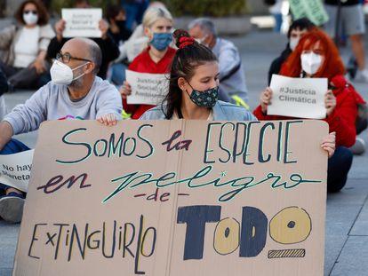 """Ativistas protestam em Madri em 25 de setembro, Dia Global da Ação pelo Clima. No cartaz, lê-se: """"Somos a espécie em perigo de extinguir tudo""""."""