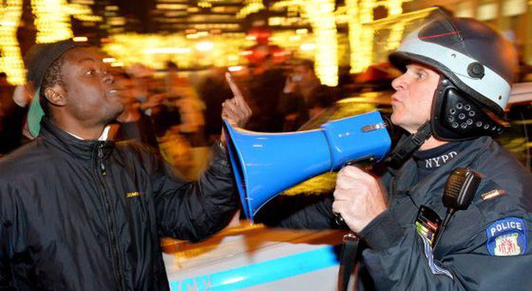 Manifestante discute com policial em Nova York.