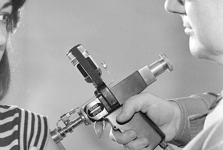 Médico vacina mulher contra a gripe suína em 1976.