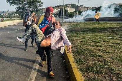 Manifestante ferido é levado durante protesto em Caracas, em maio de 2017.