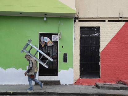 Um pintor de paredes caminha com uma escada nas costas enquanto trabalha nas fachadas das casas de San Cristóbal, em 18 de agosto passado, em Lima.