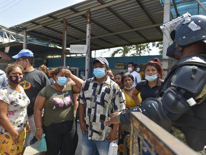 Parentes de presidiários mortos aguardam informações do lado de fora da prisão de Guayaquil, nesta quinta-feira.