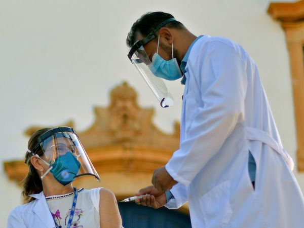Margarida Maria Honorio, a health professional for over 30 years, is inoculated with the Sinovac Biotech's CoronaVac against COVID-19 by the city's mayor, doctor Renilton Ribeiro Coelho, in front of the Santo Antonio church in Mateus Leme, Minas Gerais state, Brazil, on January 19, 2021 in a symbolic ceremony. (Photo by DOUGLAS MAGNO / AFP)