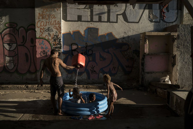 Homem banha crianças em uma favela do Rio de Janeiro.