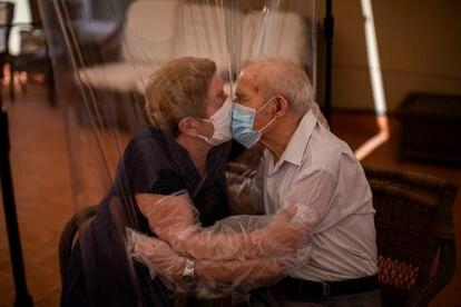 Agustina Cañamero, 81, d Pascual Pérez, 84, se beijam com a proteção de máscaras e um plástico em Barcelona.