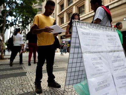 Pessoas procuram vagas de empregos em cartazes no centro de São Paulo.