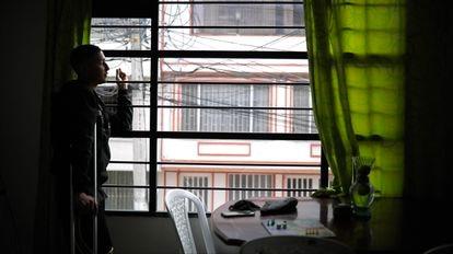 Diego Barceló fuma na janela do seu apartamento, em Bogotá.