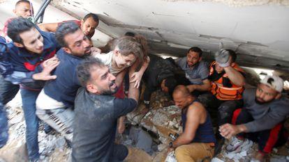 Agentes de resgate carregam menina em meio a buscas por sobreviventes após bombardeio de Israel.