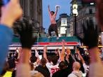 England football fans in Piccadilly Circus, central London, celebrate the victory in the Euro 2020 round of 16 soccer championship match between England and Germany. (Yui Mok/PA via AP)