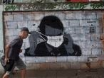 A man walks past a graffiti of Brazil's President Jair Bolsonaro wearing a protective mask during the new coronavirus outbreak in Rio de Janeiro, Brazil, Tuesday, April 7, 2020. (AP Photo/Silvia Izquierdo)