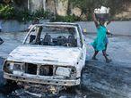 Dos mujeres frente a un coche quemado frente a la Embajada de Canadá en Puerto Príncipe. Varios cientos de policías y simpatizantes se manifestaron el 27 de octubre en la capital de Haití exigiendo mejores salarios.