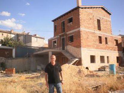 O prefeito de Olmeda da Encosta (Cuenca), José Luis Regacho, posa adiante de uma das parcelas leiloadas, onde seu novo dono já se está construindo uma casa.