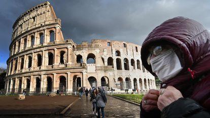 Um homem com máscara diante do Coliseu, em Roma.