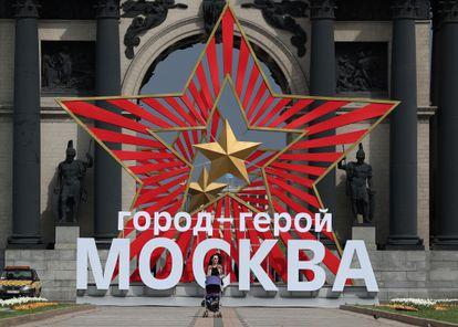 Uma mulher caminha em frente a um painel que comemora a vitória do Exército Vermelho sobre a Alemanha nazista, na última quinta-feira, em Moscou.