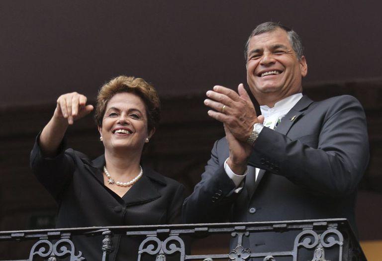 Os presidentes do Brasil, Dilma Rousseff (à esq.), e do Equador, Rafael Correa, acenam de uma sacada em Quito.