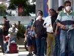 Un grupo de personas con mascarillas espera en la cola para entrar a un banco en Bogotá este lunes.